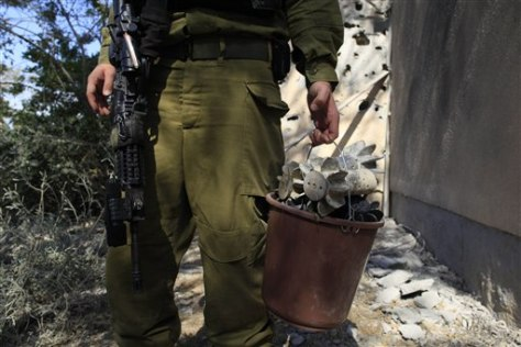 Image: An Israeli soldier holds a bucket full of mortar shells