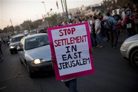 Image: A Palestinian holds a banner during a weekly demonstration