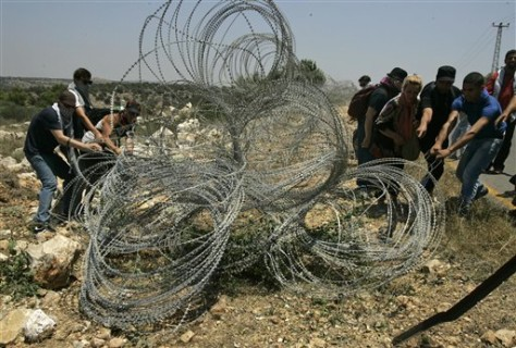 Image: Palestinians and foreign activists damage a part of the Israeli security barrier near the West Bank town of Qalqiliya