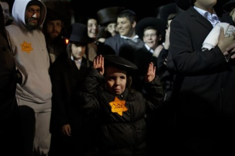 Image: An Orthodox Jewish child wears a Star of David patch