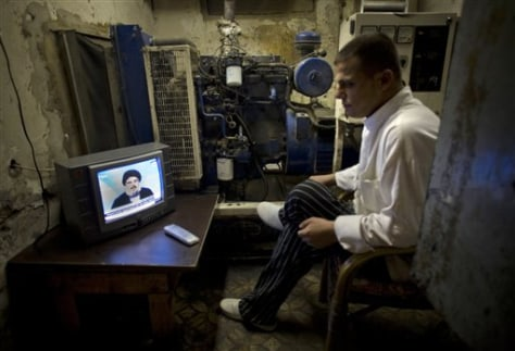 Image: A man watches the speech of Hezbollah leader Hassan Nasrallah