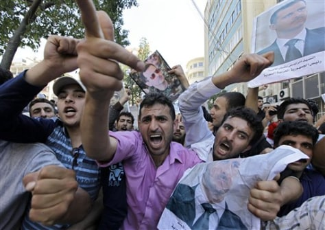 Image: Pro-Assad Syrians shout slogans as they carry pictures of the president during a sit-in in front of the Syrian embassy in Beirut, Lebanon, on Sunday.