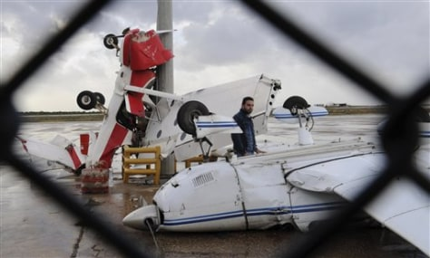 Image: A man checks damaged pilot training planes