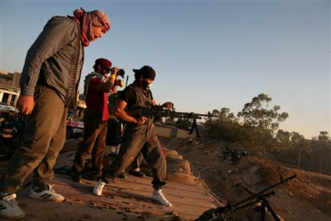 Image: Libyan rebel fighter fires a machine gun