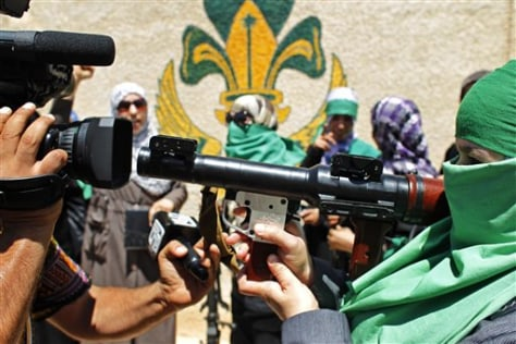 Image: A journalist photographs a Libyan woman who has a weapon