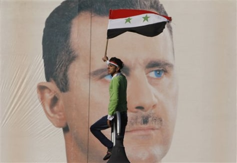 Image: Pro-Syrian regime protester waves a national flag in front of portrait of Syrian President Assad