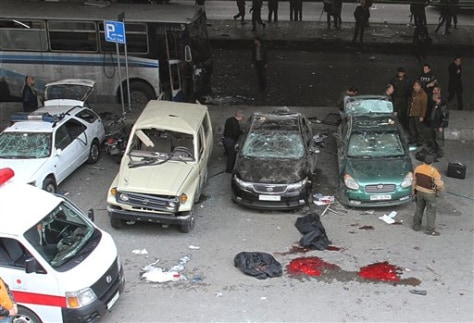 Image: Investigators inspect damaged police cars at the scene of a bomb in Midan, Damascus
