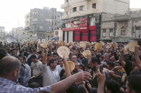 Image: Syrian men carry bread loaves
