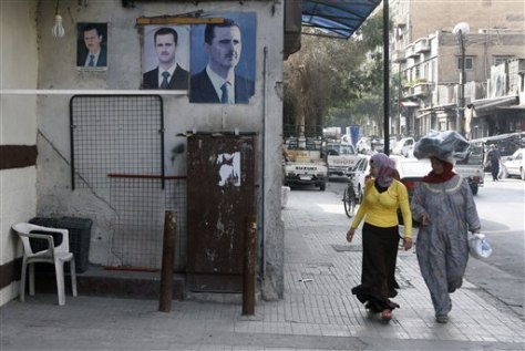 Image: Woman stroll past posters in Syria