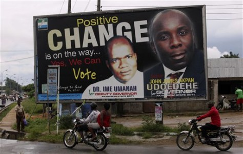 Image: Motorcyclists ride past a campaign billboard