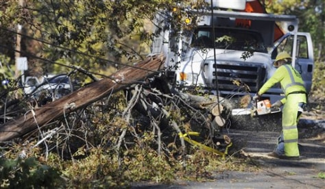 Image: Worker removes trees around downed lines in Simsbury, Conn.