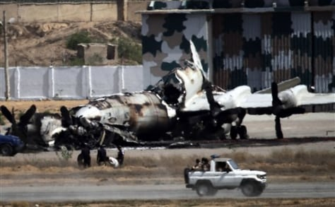 Image: Pakistani troops drive past a wreckage of a gutted aircraft destroyed by militant attacks at a Pakistan Navy base in Karachi, Pakistan