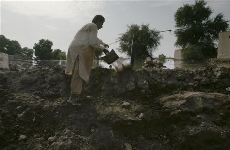 Image: Village Ghulam Raza works to reinforce embankment