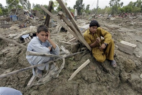 Image: Pakistani villagers sit on collapsed houses