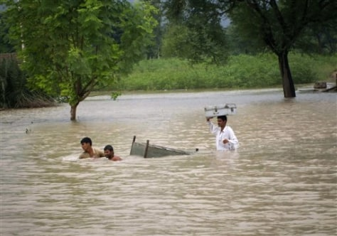 Image: Pakistani villagers pull their belongings through floodwaters