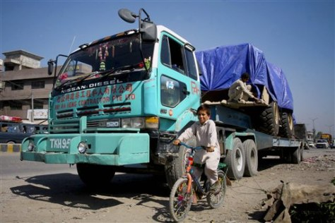 Image: Child pedals past a truck