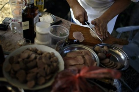 Image: Participant of the so-called 7th annual World Testicle Cooking Championship prepares a dish in the village of Ozrem