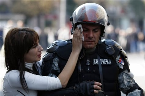 Image: Member of Serbian riot police is assisted by a passer-by