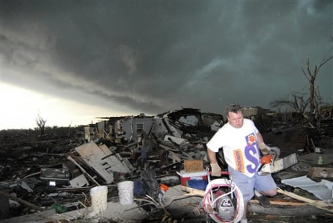 Image: Mark Siler carries salvaged items from the house of a friend following a devastating tornado in Joplin, Mo.
