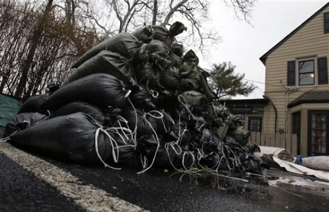 Image: A pile of sandbags sits in a parking lot