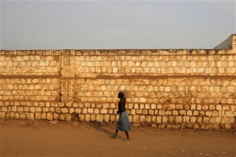 Image: Woman walks along a stadium wall