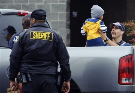 Image: Metro Fire and Sheriff department personnel entertain a toddler