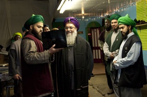 Image: Sheik Abdul Kerim al-Kibrisi, center, speaks via Skype on a laptop computer to a fellow Sufi Muslim