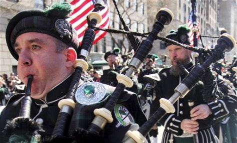 Image: Joseph O'Keefe, left, plays a bagpipe as the Department of Sanitation of New York's Emerald Society Pipes and Drums marches during the St. Patrick's Day parade in New York last year