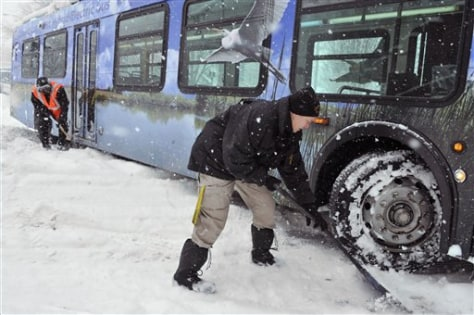 Image: Hartford Police Officer Claudette Kosinski, right, and Joe Little of CT Transit shovel under the wheels of a bus