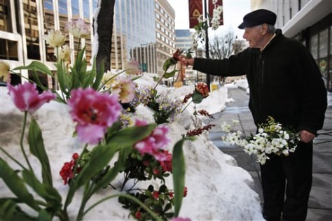 Image: Phil Caruso of Caruso Florist, puts flowers in the snow outside the shop in Washington.