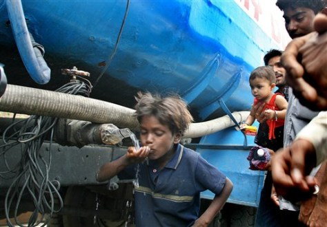 IMAGE: BOY DRINKS FROM WATER TRUCK