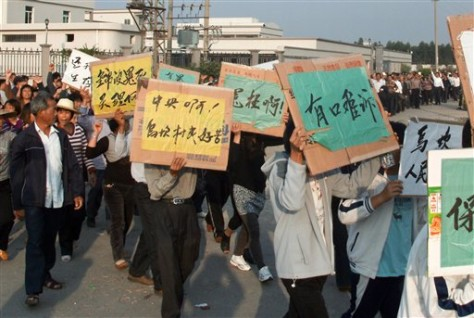 Image: Villagers hold placards chanting slogans during a protest in Wukan village, China