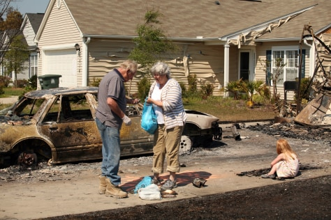 Image: People search burned out homes