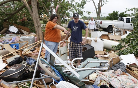 Image: People look through debris