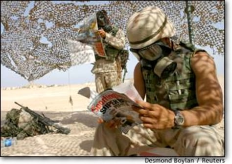 Image: U.s. Marine Reads Wearing Respirator During Gas Attack Drill In An Undisclosed Location In The Kuwaiti Desert