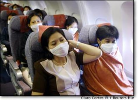 Image: Passengers Wear Protective Masks Against Sars On Flight To Singapore