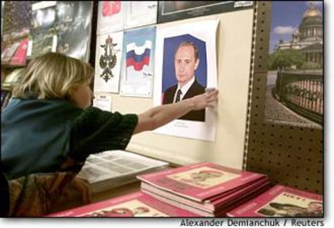 Image: Russian Shopkeeper Hangs Portrait Of President Vladimir Putin In St. Petersburg