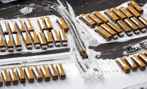 Image: A front end loader moves mounds of snow away from Columbus City School buses.