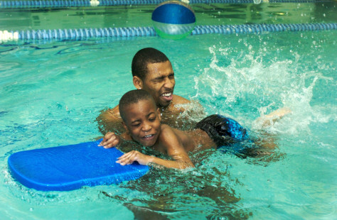 Image: Swimmer Cullen Jones helps Tavion Traynham with the kick board