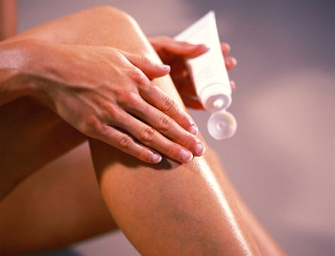 Image: Woman putting lotion on legs