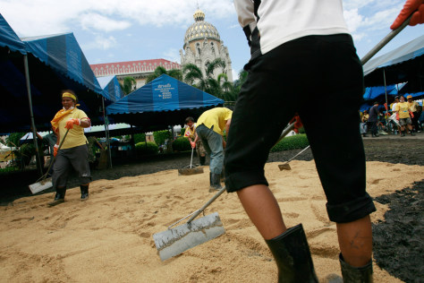 Image: Anti-government demonstrators disperse sand over muddy grounds of the Government House in Bangkok