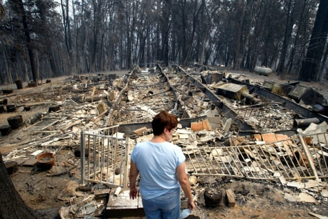 Image: Woman surveys remnants of burned house.