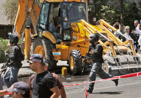 Image : Israelis run past a construction vehicle