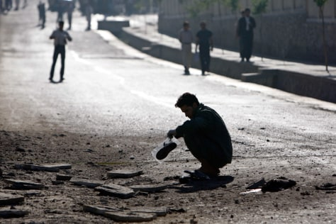 A crime investigating team works at the site after a suicide bombing in Kabul