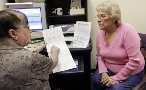 Image: A volunteer counsels a medicare recipient about her plan