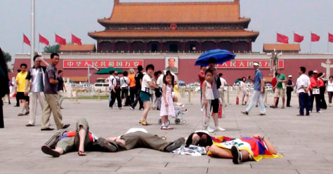 Image: foreign activists draped in Tibetan flags lying on the pavement at Tiananmen Square