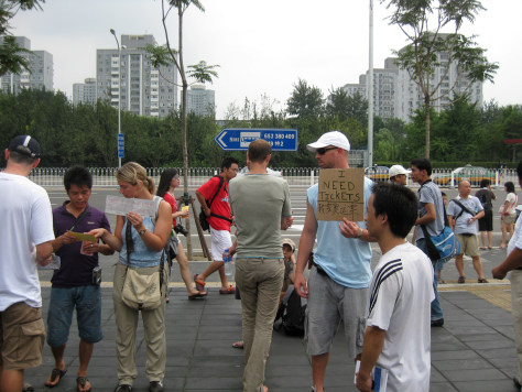 "Image: Benny Daniel, holding the ""I need tickets"" sign, works the sidewalk outside the Beitucheng subway station"