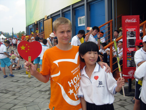 Image: Tobias Harens, left, and Zheng Mo Xuan hold up their gifts outside the beach volleyball arena on Tuesday.
