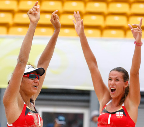 Image: Andrezza Chagas and Cristine Santanna of Georgia celebrate their victory after their women's preliminary round beach volleyball match against Russia at the Beijing 2008 Olympic Games