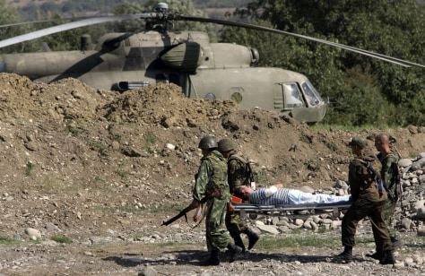 Image: A wounded Russian pilot is carried to a helicopter following a prisoner swap in Igoeti, Georgia
